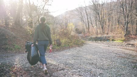 coletando : Environmental pollution, volunteering concept. A young woman with a black plastic bag and gloves in her hands walks on nature near the river Stock Footage