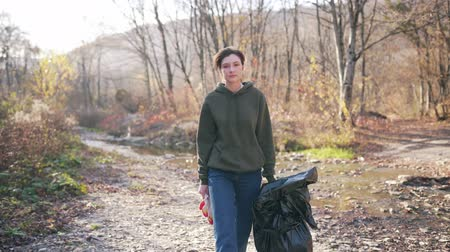 vybírání : Portrait of a beautiful volunteer girl in the sun with a plastic bag in the autumn landscape. Garbage and plastic collection outdoors