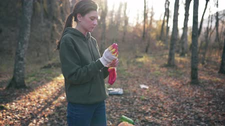 coletando : Preparation for the collection of garbage and plastic waste in the autumn forest. Young woman volunteer puts on gloves to recycle the reserve from debris