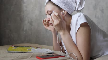 pomačkání : Attractive girl with a towel on her head and patches reads a magazine and listens to music. Eco moisturizing cosmetics. Relaxed lifestyle
