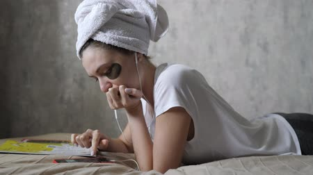 listening music : Caucasian woman chooses music on a smartphone while lying on a couch in headphones. Woman portrait with patches under the eyes and in a towel