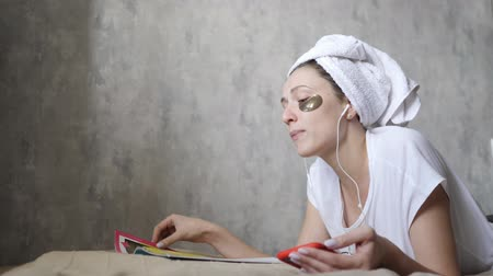 listening music : Skin care and listening to music on headphones. Young woman with a smartphone enjoys audio and reads a magazine on the couch Stock Footage
