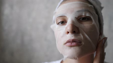 procedimento : Portrait of a young caucasian woman in a moisturizing mask on her face and with a towel on her head. Healthy lifestyle and facial rejuvenation