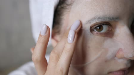procedimento : Close-up moisturizing white mask on a female face. Natural wellness care, gray background, close-up