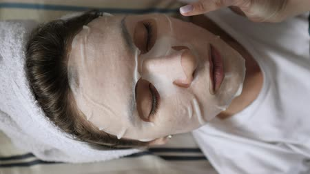 hazugság : Beauty and face care - a girl in a white cleansing mask on her face is resting before a working day, lying on a beautiful pillow