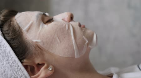 yalan : Female profile in a mask on a background of a gray wall. Skin moisturizer made from natural cosmetics