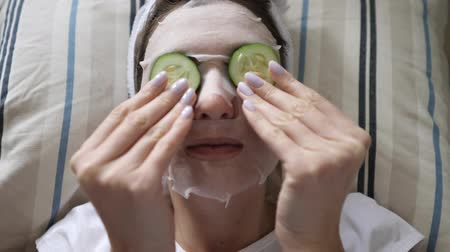 okurka : Beautiful skin care - a young woman in a white moisturizing mask puts round cucumbers on her eyes, lying on a couch Dostupné videozáznamy