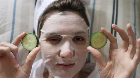 zelené oči : A young woman in a cleansing mask and a towel looks at the camera and holds round cucumbers in her hands. Wellness, beauty product and skincare