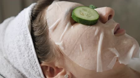 regenerating : Facial beauty treatment with fresh cucumbers and a moisturizing face mask. Woman with a white towel on her head resting on a pillow