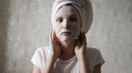 procedimento : Caucasian woman in a moisturizing mask on her face knots a white towel on her head and looks at the camera. Cleansing Facial, Rejuvenation, Makeup and Relax Stock Footage