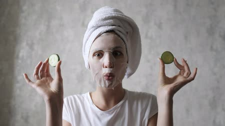 regenerating : A woman in a face mask is having fun with round cucumbers, looking at the camera and fooling around. Natural Regenerating Skin Care Stock Footage