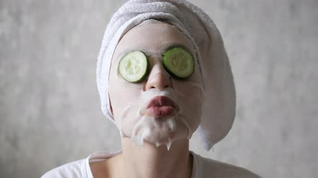 regenerating : Fun, face care, lifting and hydration. Round cucumbers fall from the eyes of a young beautiful woman