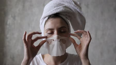 tomar : A young woman removes a moisturizing mask from her face and reapplies it to her neck. Beauty, skin care, cosmetic procedure