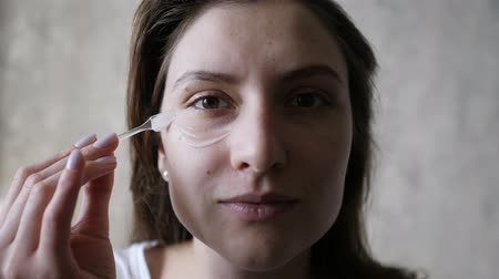 уход за телом : Beautiful young woman is applying a transparent moisturizer against wrinkles on her face. Facial care, natural skin, cosmetics