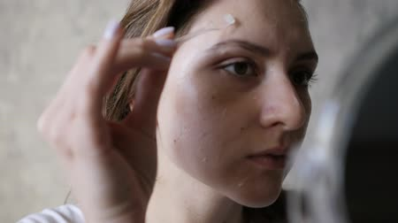 Łopata : Female beauty and well-being. Wellness skin care closeup. A girl looks in a small mirror and applies a transparent cream on her face with a brush