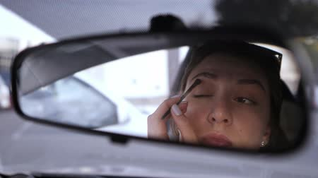 distraído : A beautiful Caucasian girl looks in the rear view mirror of the car and puts shadows on her eyes. Violation of the law in the car. A woman gathers in transport Vídeos