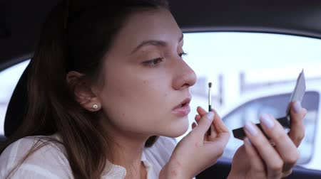 distraído : Portrait of a businesswoman doing makeup in a car. Applying eye shadows with a brush. Girl gets into the eye and winces in pain when applying cosmetics