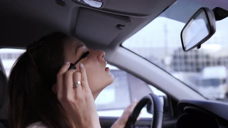rímel : Apply mascara using a brush. Illegal driving. Beautiful young woman looks in the rearview mirror for applying make-up
