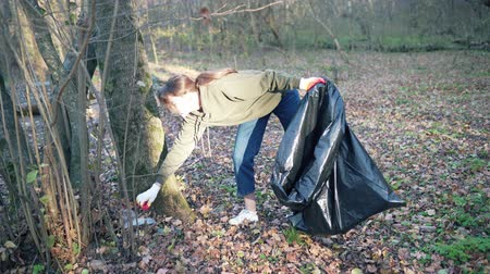 щит : A woman walks through the woods and removes plastic bottles. Garbage bag to clean the environment from pollution