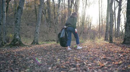 coletando : Collect garbage in the fall in a trash bag. A woman in the forest saves nature from destruction. The worlds environmental problems. Wide static plan