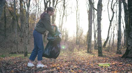 activist : A beautiful girl goes against the background of trees and sunlight and cleans nature of plastic. Clean outdoor space