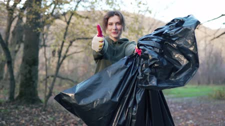 coletando : Portrait of a beautiful volunteer woman with a garbage bag in her hands. Holding a campaign to clean up the forest from debris. The girl smiles and shows like Stock Footage
