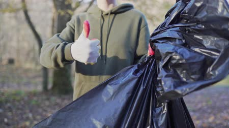 щит : A female volunteer shows like and a black garbage bag, after clearing the forest of plastic. Environmental issues