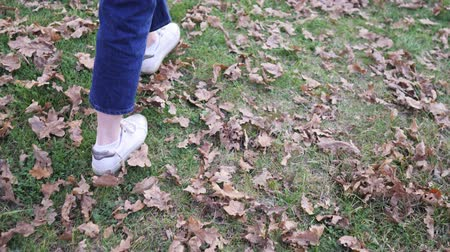 outubro : A girl walks on the lawn in jeans and sneakers, warm winter. Ankles without socks in autumn weather