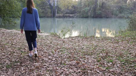 outubro : Slender girl in denim goes to the bank of the river. Autumn walk in the park. Polluted water in the city Stock Footage