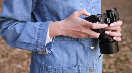 tomar : Black camera in female hands, close-up. A woman in denim clothes looks at and chooses the footage on a mirrorless camera in the street