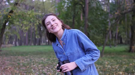 tomar : Portrait of a professional freelancer with a camera in hand in the autumn forest at sunset. The girl smiles and looks into the camera, a wide static shot Stock Footage