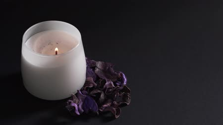 Aromatherapy concept - a womans hand sets fire to a white candle isolated on a black background. Dry fragrant flowers for relaxation and meditation in the spa
