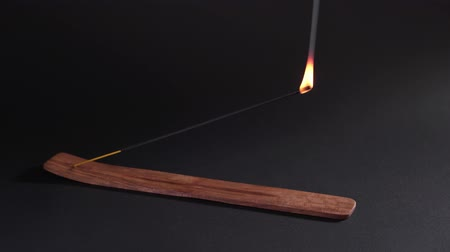 A womans hand sets fire to an aromatic stick in a stand on a black background. Spiritual smoke, strong smell for the ceremony. Natural aromatherapy. Black background, static shot.