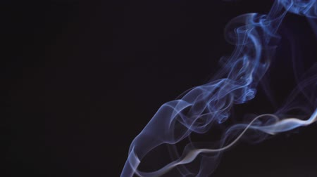 Blue isolated smoke on a black background. The mist is moving up, color of the indigo. The fog dissolves beautifully into different shapes in the air