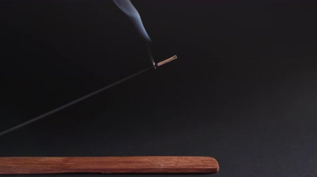 дзен : Incense burns on a beautiful wooden stand, on a black background. Aromatherapy for health and prosperity. The concept of meditation, zen and self-knowledge Стоковые видеозаписи