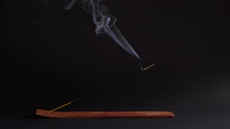 The aromatic stick smokes in the stand on a black background. Incense for relaxation and meditation, Asian subject. Buddhism, natural flow and magic
