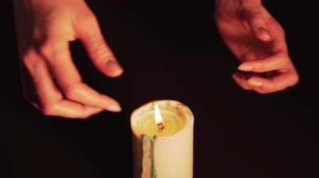Mysterious magic close-up - womens hands conjure over a burning candle in isolation on a black background. The concept of prediction, clairvoyance and divination