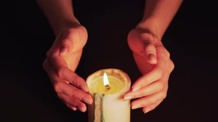 Womens hands above the burning candle close-up. Magic fire, the witch predicts. Isolate on a black background, a static shot