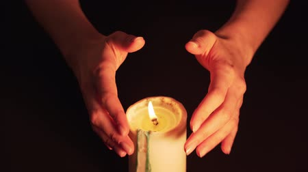 A clairvoyant witch prediction over a candle. Womens hands over the flame are isolated on a black background. The concept of paranormal, prediction of the future and mysticism