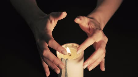 witchcraft : Mystical divination on a black background. A fortune teller reads the future in the flames of a burning candle on a black background. Isolated static shot