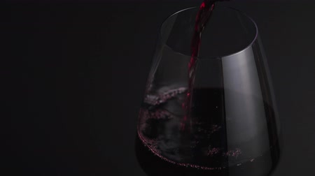 Red wine flows into a fragile glass on a black background. Sommelier fills a sweet alcoholic beverage glass in a bar close-up, isolated Wideo