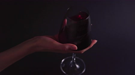 The smell of wine - a womans hand rotates a glass on a black background. A professional in a bar or restaurant tastes an alcoholic beverage