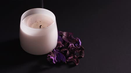 Aromatic candle blown out, dry flowers with a pleasant smell for relaxation in the spa. Close-up, static shot on a black background, isolated