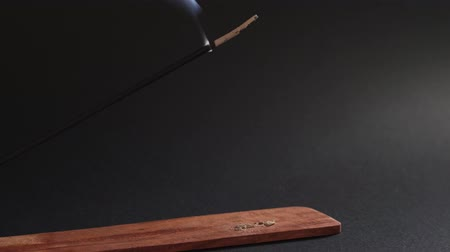 Eastern aromatic smoke. Incense stick burns in a wooden stand on a black background. Natural smoke moves up