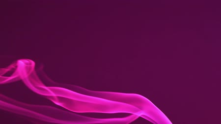 Pink smoke on a dark background. Bright fog turns left and up