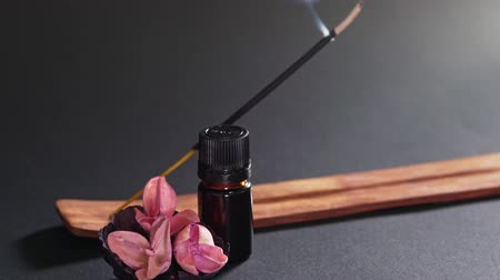 Aromatic oil in a black small jar, flowers and steaming incense. A static shot against a black background. The smell of the east, the concept of massage and meditation Wideo
