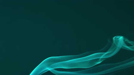 Beautiful green smoke goes up against a dark background. Abstract fog is moving slowly