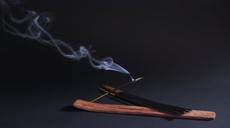 сжигание : Therapeutic oriental smoke. Aromatherapy, relaxation and yoga. Smoke from aroma sticks moves on a black background