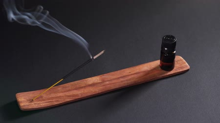 сжигание : Aromatic oil and steaming incense on a wooden stand against a dark background. Items for aromatherapy, meditation and massage