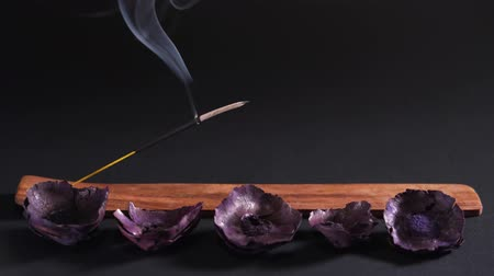 сжигание : Eastern aromatherapy. Dry flowers and steaming incense on a dark background